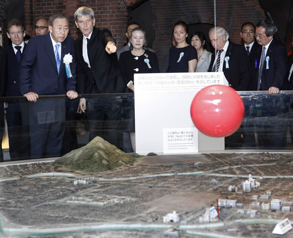 U.N. Secretary-General Ban Ki-moon, left front, looks at a scale model of the destruction caused by the Aug. 6, 1945 atomic bombing on Hiroshima, at Hiroshima Peace Memorial Museum in Hiroshima, western Japan, Friday, Aug. 6, 2010. (AP Photo/Shuji Kajiyama)