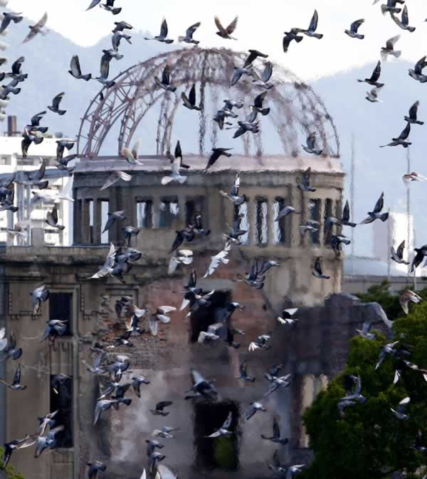 Doves fly past the gutted Atomic Bomb Dome during the 65th anniversary ceremony of the 1945 atomic bombing at Hiroshima Peace Memorial Park in Hiroshima, western Japan, Friday, Aug. 6, 2010.(AP Photo/Shuji Kajiyama)