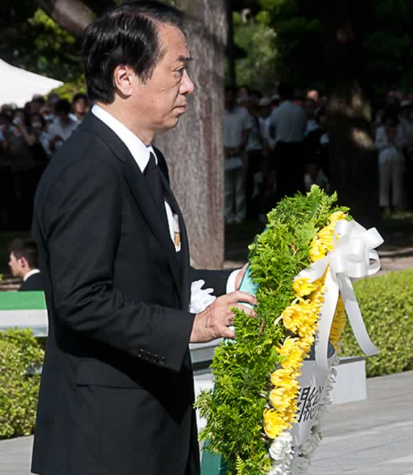 In this photo provided by the City of Hiroshima, Japanese Prime Minister Naoto Kan, carries a wreath to offer at the cenotaph for the atomic bomb victims during the 65th anniversary of the 1945 atomic bombing at the Peace Memorial Park in Hiroshima, western Japan, Friday, Aug. 6, 2010. (AP Photo/City of Hiroshima)