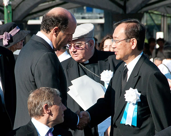 In this photo provided by the City of Hiroshima, U.S. Ambassador to Japan John Roos, left, greets Hiroshima city's Mayor Tadatoshi Akiba on his arrival at the Hiroshima Peace Memorial Park to attend the 65th anniversary of the world's first atomic bombing in Hiroshima, western Japan Friday, Aug. 6, 2010. The United States sent its first ever delegation to the ceremony marking the anniversary of the attacks. (AP Photo/City of Hiroshima)