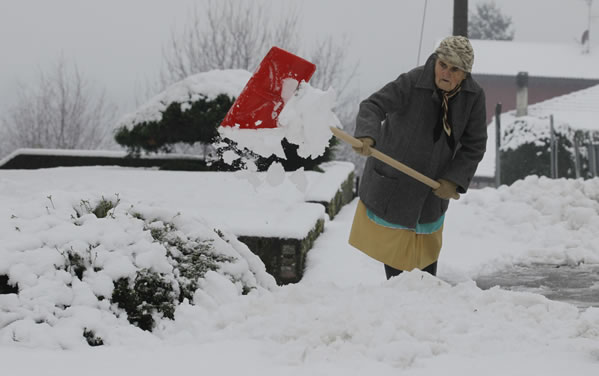 A woman clears the snow in front of her house in Appiano Gentile, near Milan in northern Italy, Wednesday, Dec. 1, 2010. Heavy snowfalls disrupted traffic in Northern Italy, while rains are causing preoccupation in central Italy as many rivers are at risk of overflowing their banks. (AP Photo/Luca Bruno)