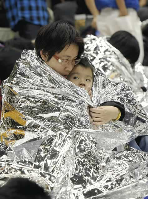 A child is held by a woman in a disaster sheet...