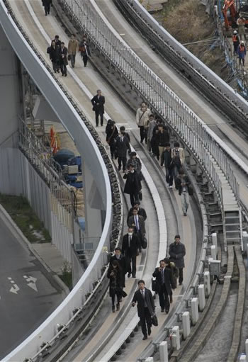 Yurikamome train passengers walk on the elevated track towards Shiodome Station in Tokyo's Shiodome district near Tokyo Bay Friday, March 11, 2011, shortly after a 7.9-magnitude earthquake has struck off Japan's northeastern coast. (AP Photo/Koji Sasahara)