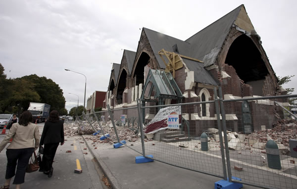 People walk past a church in Christchurch, New Zealand, which was destroyed after an earthquake struck Tuesday, Feb. 22, 2011. The 6.3-magnitude quake collapsed buildings and is sending rescuers scrambling to help trapped people amid reports of multiple deaths. (AP Photo/NZPA, Pam Johnson)