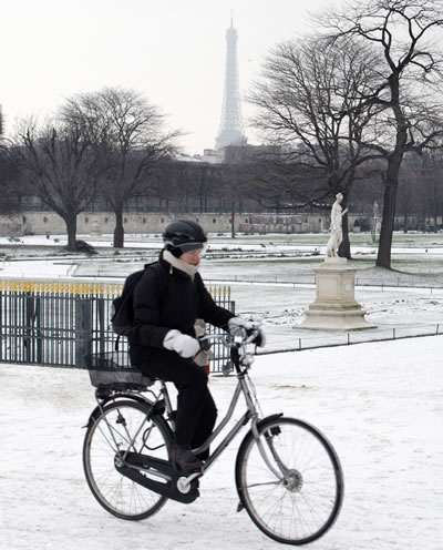 A woman rides her bicycle pass the Tuileries garden in Paris as freezing temperatures swept the French capital Thursday Dec. 2, 2010. Heavy snow and subzero temperatures swept across Europe, killing at least eight homeless people in Poland, closing major airports in Britain and Switzerland, and causing delays to rail and road traffic across the continent.(AP Photo/Remy de la Mauviniere)