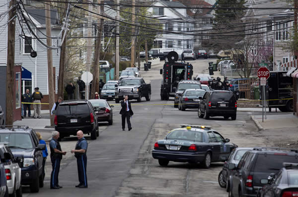 Police presence grows in the neighborhoods of Watertown, Mass., Friday, April 19, 2013, as a massive search involving hundreds of heavily armed law enforcement officials continues for one of two suspects in the Boston Marathon bombing. A second suspect died in the early morning hours in a car chase and gun battle overnight that left one of them dead and his brother on the loose, authorities said Friday. (AP Photo/Craig Ruttle)