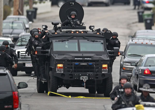 "<div class=""meta ""><span class=""caption-text "">Police patrol through a neighborhood in Watertown, Mass., while searching for a suspect in the Boston Marathon bombings, Friday, April 19, 2013. The bombs that blew up seconds apart near the finish line of the Boston Marathon left the streets spattered with blood and glass, and gaping questions of who chose to attack and why. (AP Photo/Charles Krupa)</span></div>"