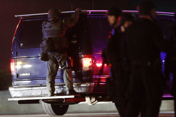 "<div class=""meta ""><span class=""caption-text "">A police officers rides on the back of a van at a staging area as a manhunt is conducted for a suspect Friday, April 19, 2013, in Watertown, Mass. One of two suspects in the Boston Marathon bombing is dead and a massive manhunt is underway for another, authorities said early Friday April 19, 2013. Residents of Watertown, a Boston suburb, have been advised to keep their doors locked and not let anyone in. (AP Photo/Matt Rourke)</span></div>"