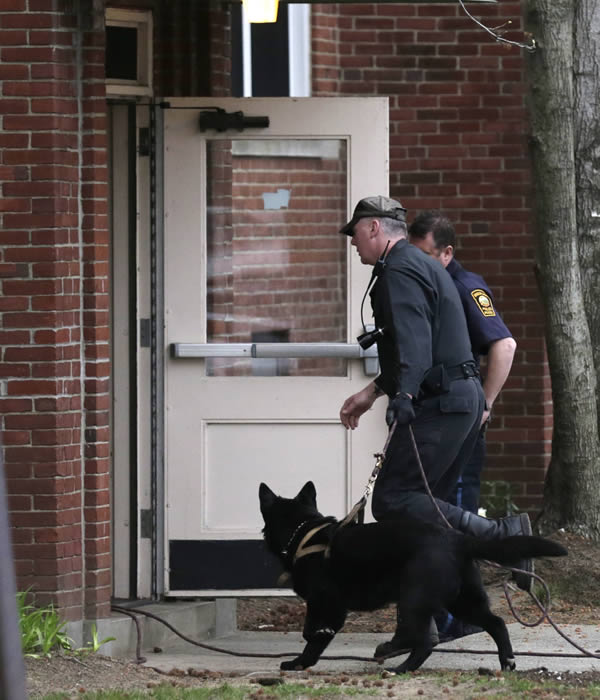 A police officer enters an apartment building with his dog while searching for a suspect in the Boston Marathon bombings in Watertown, Mass., Friday, April 19, 2013. The bombs that blew up seconds apart near the finish line of the Boston Marathon left the streets spattered with blood and glass, and gaping questions of who chose to attack and why. (AP Photo/Charles Krupa)