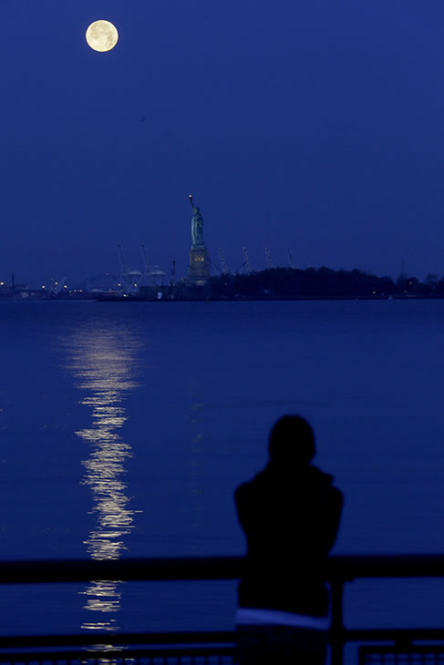 "Christina Magnotta, of White Plains, N.Y., looks on as the supermoon glows over the Statue of Liberty and the Hudson River, Sunday, June 23, 2013, in New York. The larger than normal moon called the ""Supermoon"" happens only once this year as the moon on its elliptical orbit is at its closest point to earth and is 13.5 percent larger than usual. (AP Photo/Julio Cortez)"