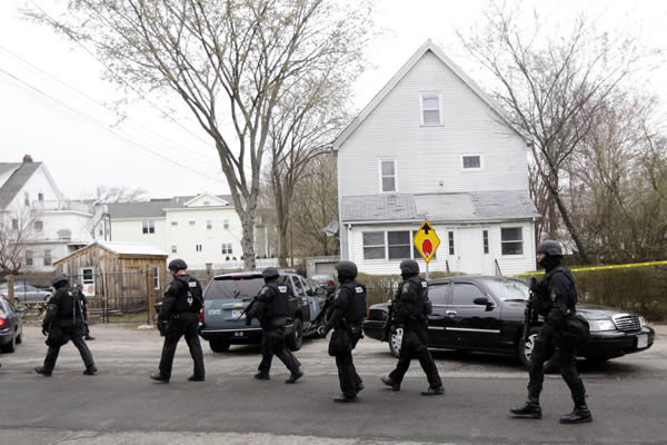 Police in tactical gear conduct a search for a suspect in the Boston Marathon bombings, Friday, April 19, 2013, in Watertown, Mass. All residents of Boston were ordered to stay in their homes Friday morning as the search for the surviving suspect in the marathon bombings continued after a long night of violence that left another suspect dead. (AP Photo/Matt Rourke)