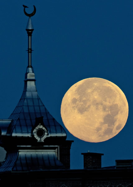A full super moon sets behind the top of one of the minarets at the University of Tampa Sunday, June 23, 2013, in Tampa, Fla. (AP Photo/Chris O'Meara)