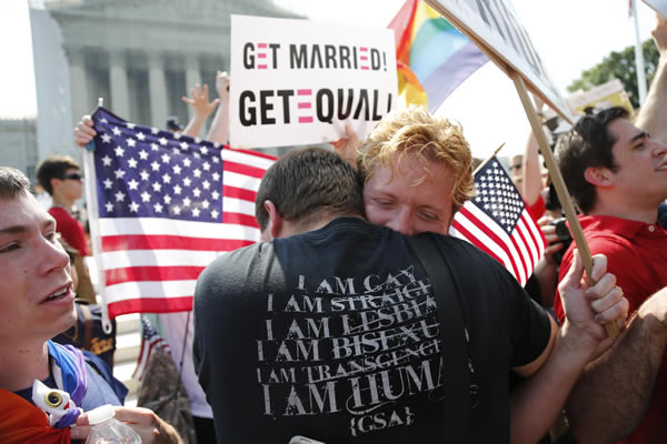 Michael Knaapen, left, and his husband John Becker, right, embrace after the Supreme Court struck down a federal provision denying benefits to legally married gay couples in front of the Supreme Court in Washington, Wednesday, June 26, 2013. In a major victory for gay rights, the Supreme Court on Wednesday struck down a provision of a federal law denying federal benefits to married gay couples and cleared the way for the resumption of same-sex marriage in California. (AP Photo/Charles Dharapak)