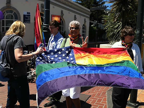 Same-sex marriage supporter smiles and holds up a flag in San Francisco's Castro neighborhood after the Supreme Court's ruling on Proposition 8.