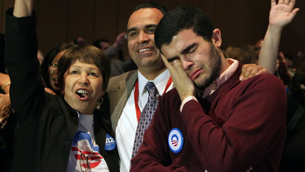 Margarita V. Rebollal, from left, and Jose M. Garcia celebrate and Alexander Andresian weeps as President Barack Obama was declared the winner Tuesday, Nov. 6. 2012, during the Nevada State Democratic Party gathering at the Mandalay Bay Resort and Casino in Las Vegas. (AP Photo/John Gurzinski)