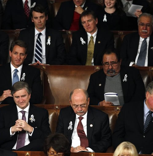 An empty seat for Rep. Gabrielle Giffords, D-Ariz. is seen on Capitol Hill in Washington, Tuesday, Jan. 25, 2011, during President Barack Obama's State of the Union address. Rep. Jeff Flake, R-Ariz. is at left, Rep. Raul Grijalva, D-Ariz. is at right. (AP Photo/Evan Vucci)