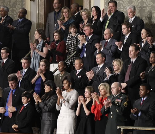 First lady Michelle Obama and guests applaud during President Barack Obama's State of the Union address in Washington, Tuesday, Jan. 25, 2011. Sitting in the first lady's box from front left are John Green, Dallas Green, Roxanna Green, Obama, Brianna Mast, Jill Biden, Sgt. Brian Mast and Brandon Ford. Second row from second to the left are Kathy Proctor, Sgt. Nicole Mohabir, Dr. Peter Rhee, Brandon Fisher, Julie Fisher, Gary Allen and Ursula M. Burns. Third row second from right is Zachary Davis and at right is Kendra Baker. (AP Photo/Charles Dharapak)