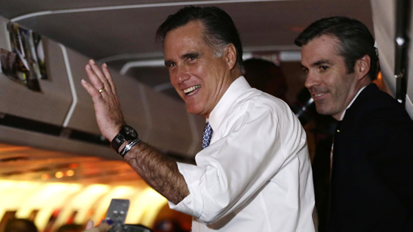 Republican presidential candidate and former Massachusetts Gov. Mitt Romney waves to reporters after he took questions on his campaign plane en route from Pittsburgh to Boston, Tuesday, Nov. 6, 2012. At right is senior adviser Kevin Madden. (AP Photo/Charles Dharapak)