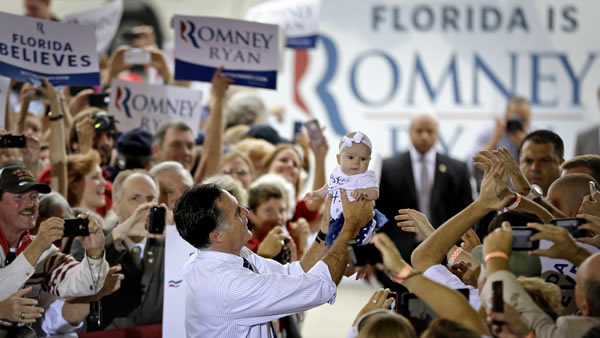 Republican presidential candidate, former Massachusetts Gov. Mitt Romney picks up a baby as he walks through the crowd before stepping on stage at a campaign event at the Orlando Sanford International Airport, Monday, Nov. 5, 2012, in Sanford, Fla. (AP Photo/David Goldman)