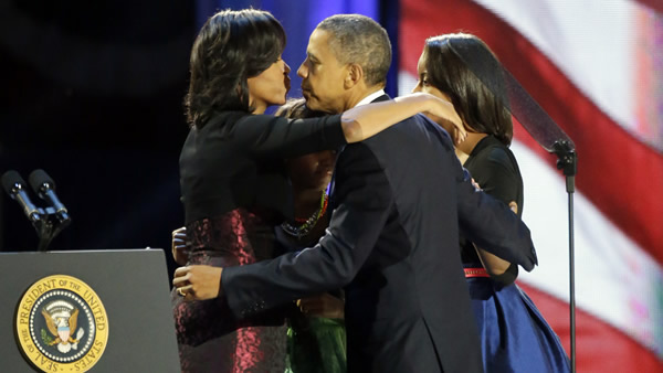 President Barack Obama kisses his wife Michelle as he walks out to the stage with his daughters Malia and Sasha at his election night party Wednesday, Nov. 7, 2012, in Chicago. President Obama defeated Republican challenger former Massachusetts Gov. Mitt Romney. (AP Photo/Pablo Martinez Monsivais)