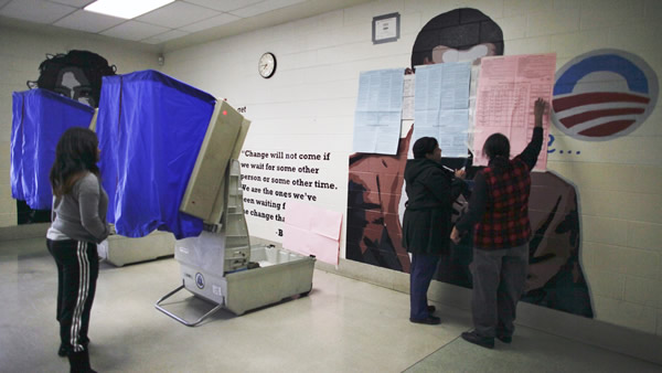 "<div class=""meta ""><span class=""caption-text "">People cast their votes Tuesday, Nov. 6, 2012, at polling location inside the Benjamin Franklin Elementary School in Northeast Philadelphia, where a mural of President Barack Obama painted on a wall behind two voting booths was ordered covered up by a Philadelphia court. The mural had been left uncovered when the polling location opened, but was ordered covered after Republicans filed a complaint. (AP Photo/ Joseph Kaczmarek)</span></div>"