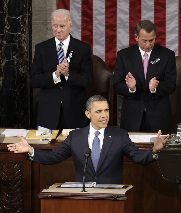 President Barack Obama gestures on Capitol Hill in Washington, Tuesday, Jan. 25, 2011, prior to delivering his State of the Union address in Washington, Tuesday, Jan. 25, 2011. Vice President Joe Biden and House Speaker John Boehner of Ohio applaud at rear. (AP Photo/Charles Dharapak)
