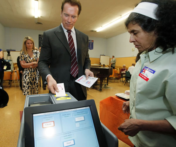 California Gov. Arnold Schwarzenegger deposits his ballot as poll worker Dhun May watches after voting at an elementary school near his home in the Brentwood district of Los Angeles, Tuesday, Nov. 2, 2010. (AP Photo/Reed Saxon)