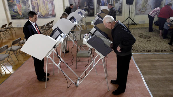 Voters stand at their voting machines at the Krishna Temple polling station Tuesday, Nov. 6, 2012, in Salt Lake City. (AP Photo/Rick Bowmer)
