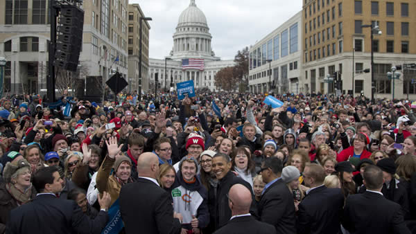 President Barack Obama looks to press cameras as he greets people in the audience at a campaign event, Monday, Nov. 5, 2012, in downtown Madison, Wis., as the state capitol building is seen in the background. (AP Photo/Carolyn Kaster)