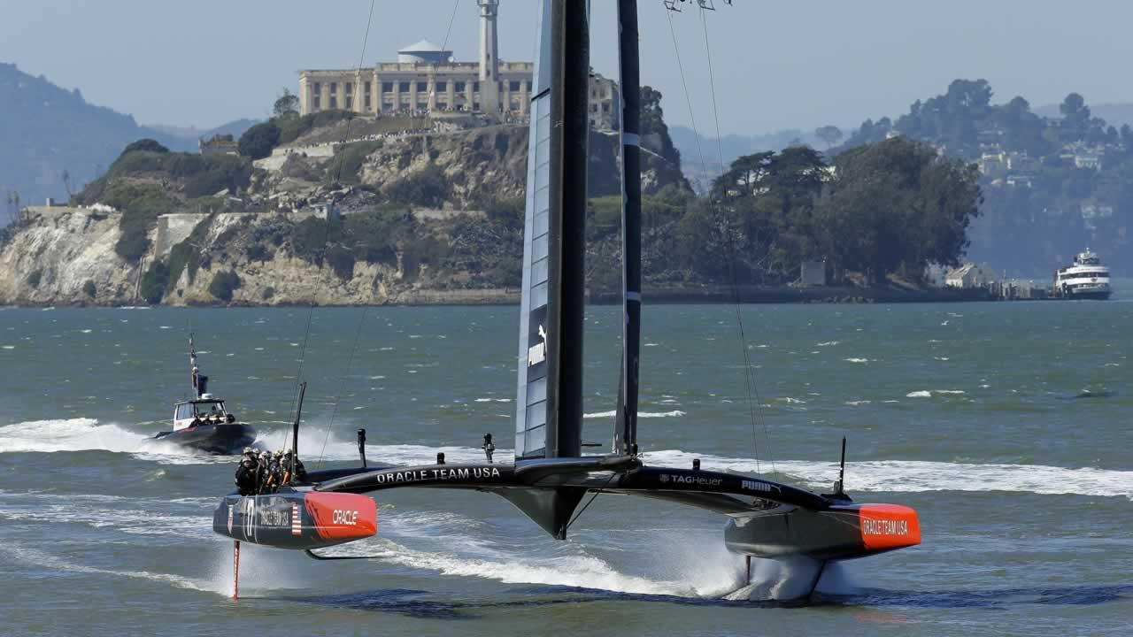 Oracle Team USA sails past Alcatraz Island after the 13th race of the Americas Cup sailing event against Emirates Team New Zealand was canceled due to excessive wind.