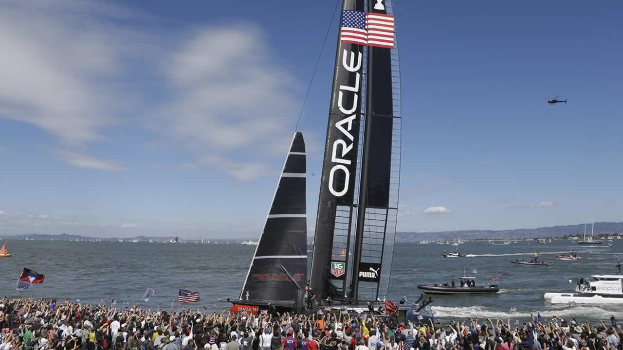 Spectators at Pier 27 cheer Oracle Team USA that won the 14th race of the Americas Cup sailing event against Emirates Team New Zealand, Sunday, Sept. 22, 2013, in San Francisco. (AP Photo/Eric Risberg)