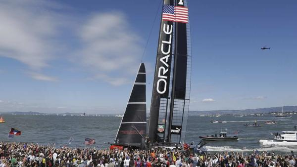 Spectators at Pier 27 cheer Oracle Team USA that won the 14th race of the America's Cup sailing event against Emirates Team New Zealand, Sunday, Sept. 22, 2013, in San Francisco. (AP Photo/Eric Risberg)