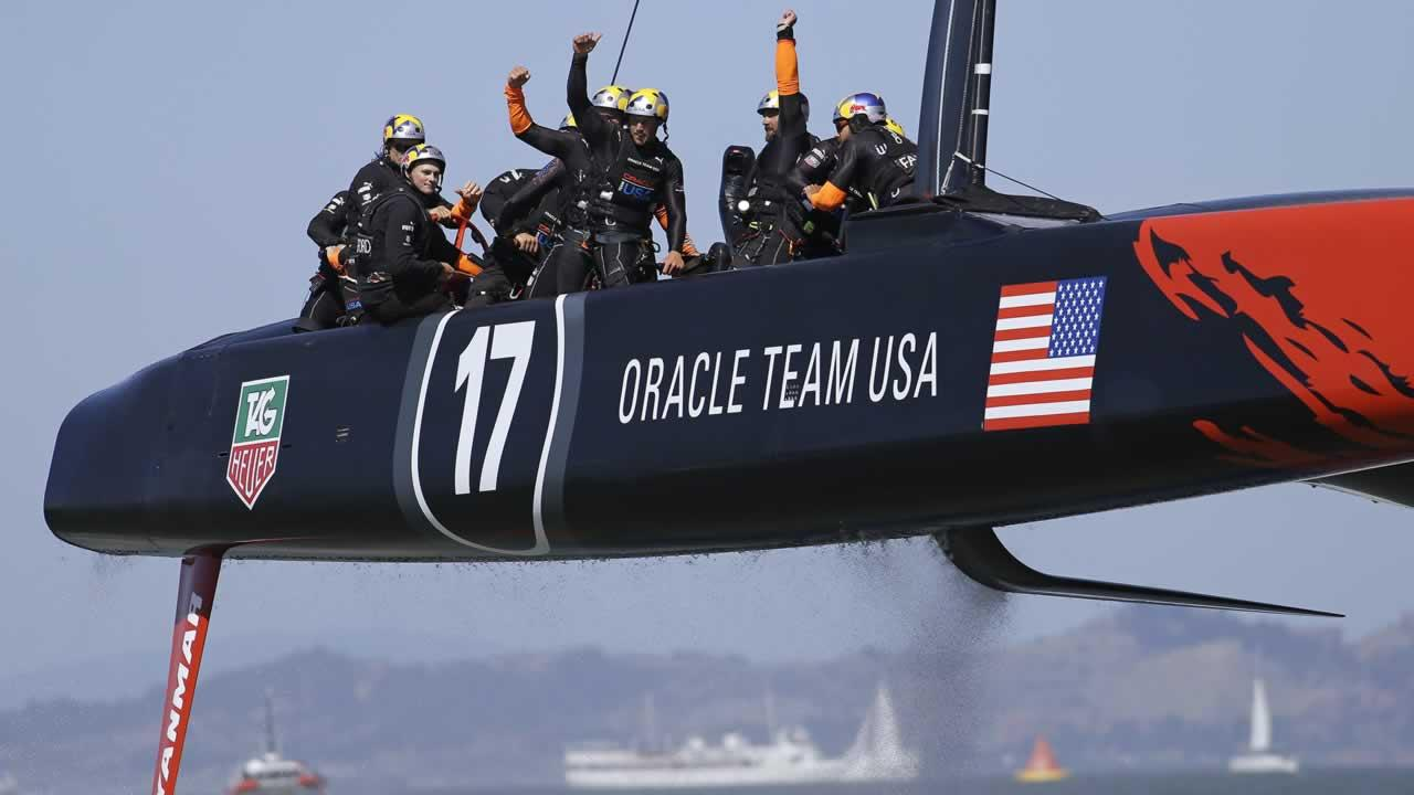The crew on Oracle Team USA waves after winning the 17th race of the Americas Cup sailing event against Emirates Team New Zealand, Tuesday, Sept. 24, 2013, in San Francisco. Oracle Team USA won both races Tuesday to even the series.