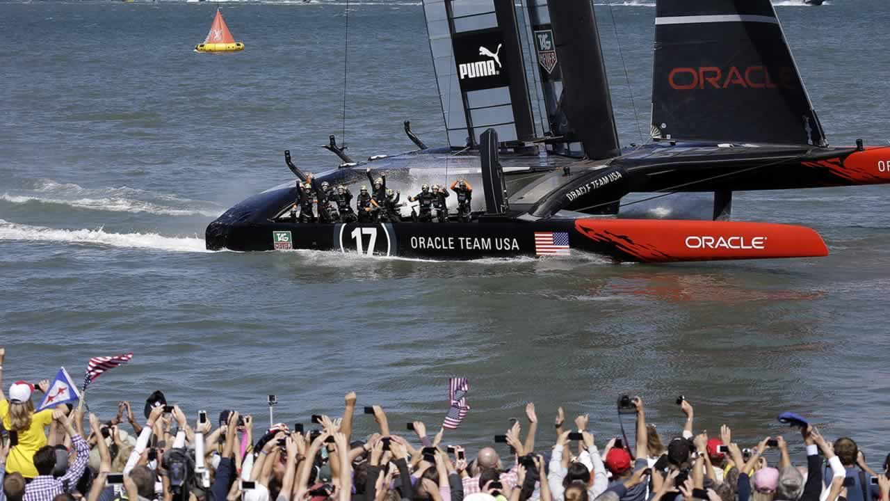 The crew on Oracle Team USA celebrates after winning the 19th race against Emirates Team New Zealand to win the Americas Cup sailing event, as fans wave in the foreground Wednesday, Sept. 25, 2013, in San Francisco. (AP Photo/Marcio Jose Sanchez)