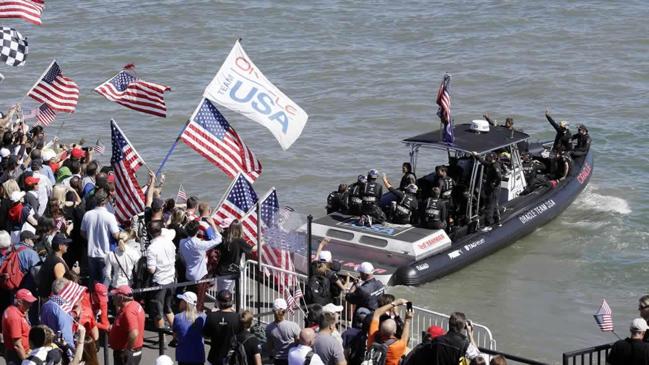 Oracle Team USA members wave at supporters as they are ferried to their catamaran before the 19th race of the Americas Cup sailing event against Emirates Team New Zealand on Wednesday, Sept. 25, 2013, in San Francisco.(AP Photo/Marcio Jose Sanchez)