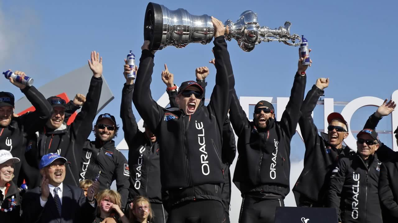 Oracle Team USA skipper Jimmy Spithill holds up the Auld Mug as they celebrate in the podium after winning the Americas Cup sailing event over Emirates Team New Zealand on Wednesday, Sept. 25, 2013, in San Francisco. (AP Photo/Marcio Jose Sanchez)