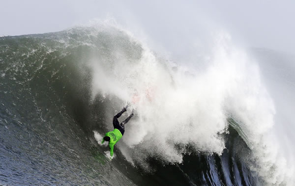 Ben Wilkinson goes tumbling into a wave during the third heat of the first round of the Mavericks Invitational big wave surf contest Friday, Jan. 24, 2014, in Half Moon Bay, Calif. (AP Photo/Eric Risberg)
