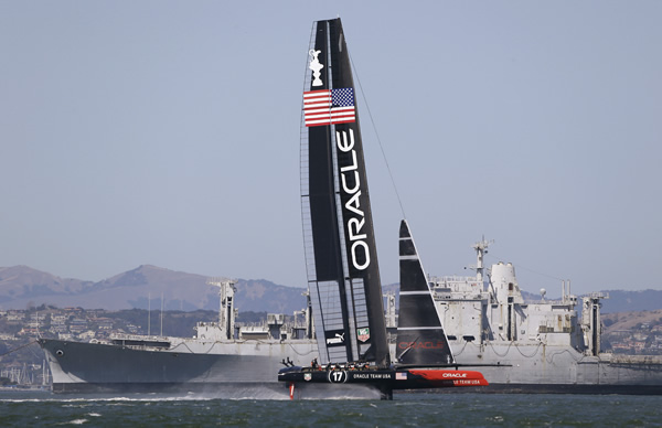 Oracle Team USA passes a decommissioned Navy ship being towed out to sea during training for the America's Cup sailing event Thursday, Sept. 5, 2013, in San Francisco. The first races between Oracle Team USA and Emirates Team New Zealand are on Saturday