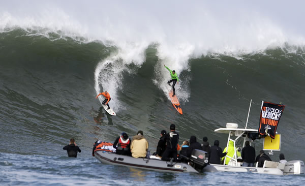 Shane Dorian, left, and Ben Wilkinson, right, catch a wave during the third heat of the first round of the Mavericks Invitational big wave surf contest Friday, Jan. 24, 2014, in Half Moon Bay, Calif. (AP Photo/Eric Risberg)