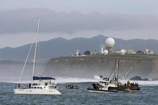 People on boats watch the third heat of the first round of the Mavericks Invitational big wave surf contest with the Pillar Point Air Force Station in the background Friday, Jan. 24, 2014, in Half Moon Bay, Calif. (AP Photo/Eric Risberg)
