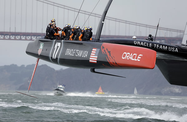 With the Golden Gate Bridge visible in the distance, an Oracle Team USA catamaran, with Jimmy Spithill at the helm, races another Oracle Team USA boat while training for the America's Cup sailing event on Saturday, Aug. 24, 2013, in San Francisco. (AP Photo/Eric Risberg)