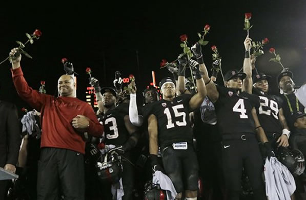 Stanford head coach David Shaw, at left, celebrates with this team after a 27-24 win over UCLA during the Pac-12 championship NCAA college football game in Stanford, Calif., Friday, Nov. 30, 2012. The Cardinal (11-2) will play the winner of the Big Ten title game between Nebraska and Wisconsin in the Rose Bowl on Jan. 1. (AP Photo/Marcio Jose Sanchez)