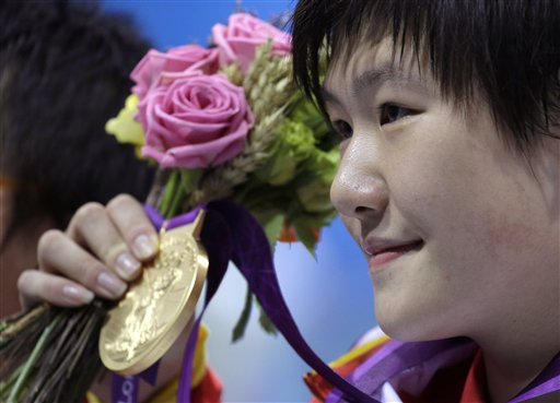 China&#39;s Ye Shiwen holds her gold medal aloft after her win in the women&#39;s 400-meter individual medley swimming final at the Aquatics Centre in the Olympic Park during the 2012 Summer Olympics in London, Saturday, July 28, 2012. Ye set a new world record with a time of 4:28:43. <span class=meta>(AP Photo&#47;Matt Slocum)</span>