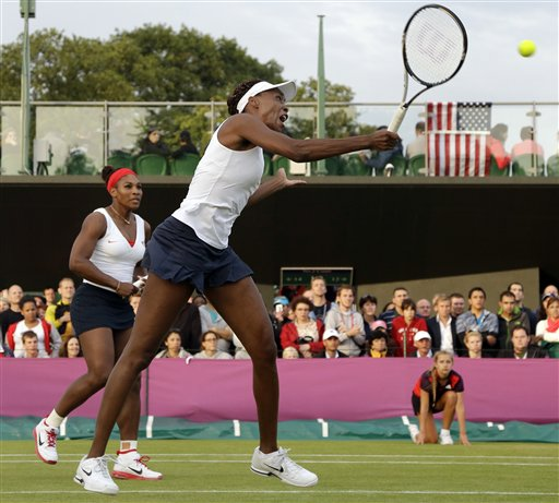 Venus Williams, right, of the United States returns as Serena, left, watches as they compete in womens doubles against Angelique Kerber and Sabine Lisicki of Germany at the All England Lawn Tennis Club in Wimbledon, London at the 2012 Summer Olympics, Tuesday, July 31, 2012. <span class=meta>(AP Photo&#47;Elise Amendola)</span>