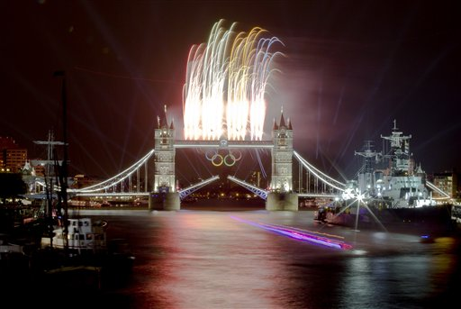A speedboat carrying the Olympic Flame leaves a trail on this slow exposure photograph as fireworks explode above the iconic Tower Bridge over the River Thames in central London, decorated with Olympic rings, during the Opening Ceremony at the 2012 Summer Olympics, Friday, July 27, 2012, in London. <span class=meta>(AP Photo&#47;Vadim Ghirda)</span>