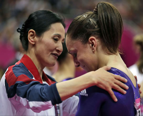 Coach Jenny Zhang consoles U.S. gymnast Jordyn Wieber as she cries after failing to qualify for the women's all-around finals during the Artistic Gymnastics women's qualification at the 2012 Summer Olympics, Sunday, July 29, 2012, in London. (AP Photo/Gregory Bull)