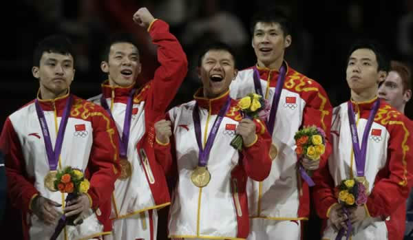 Chinese gymnasts, left to right, Feng Zhe, Guo Weiyang, Chen Yibing, Zhang Chenglong and Zou Kai celebrate winning the gold medal during the Artistic Gymnastic men's team final at the 2012 Summer Olympics, Monday, July 30, 2012, in London. (AP Photo/Julie Jacobson)