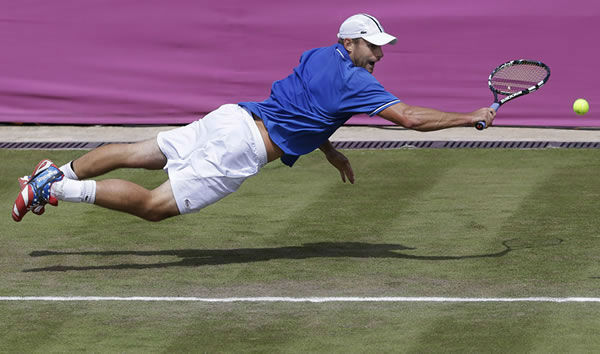 Andy Roddick of the United States dives for the ball during his match against Martin Klizan of Slovakia at the All England Lawn Tennis Club in Wimbledon, London at the 2012 Summer Olympics, Monday, July 30, 2012. (AP Photo/Elise Amendola)