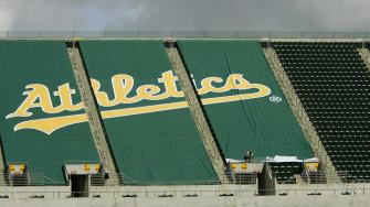 Workers affix a green tarp over upper deck seats at McAfee Coliseum Wednesday, March 15, 2006, in Oakland, Calif. (AP Photo/Ben Margot)