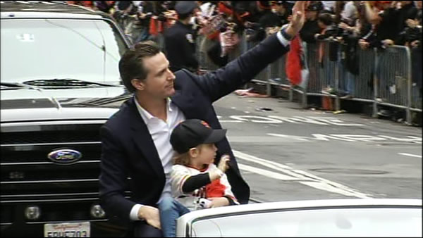 Lieutenant Governor Gavin Newsom waves to the...